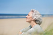 Leinwanddruck Bild - attraktive, grauhaarige Frau genießt das Meer