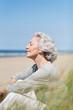 attraktive, grauhaarige Frau genießt das Meer