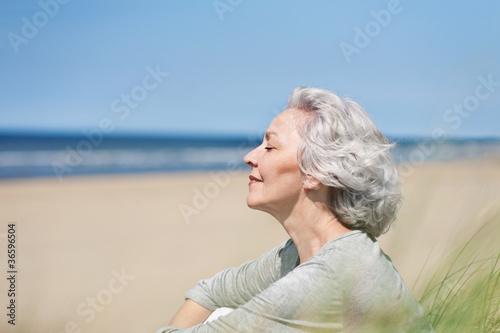 Leinwanddruck Bild attraktive, grauhaarige Frau genießt das Meer
