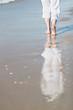 Frau im weißen Sommeroutfit spaziert am Strand