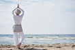 aktive Seniorin macht Yoga am Strand - 36596793