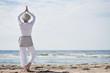 Leinwanddruck Bild - aktive Seniorin macht Yoga am Strand