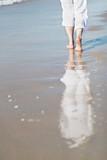 Fototapety Frau im weißen Sommeroutfit spaziert am Strand