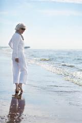 attraktive, grauhaarige Frau genießt Spaziergang am Meer