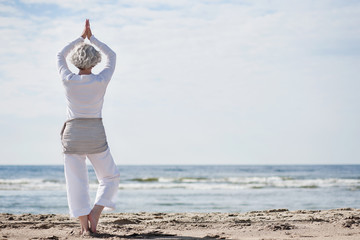aktive Seniorin macht Yoga am Strand
