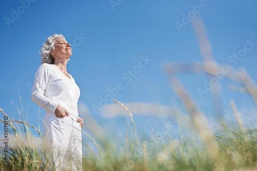 Leinwanddruck Bild attraktive, grauhaarige Seniorin genießt das Meer