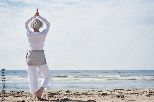 Leinwanddruck Bild aktive Seniorin macht Yoga am Strand