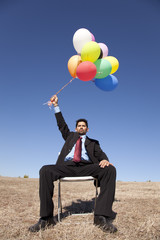 Businessman in outdoor holding balloons