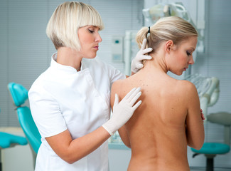 dermatologist doctor inspecting woman patient skin