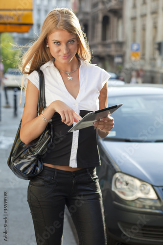 Young Business Woman with tablet computer walking on urban stree