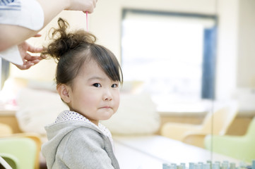 美容院で髪をセッティングする女の子