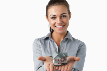 Female estate agent holding miniature house in her hands