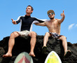 Two friend surfer sitting on a rock