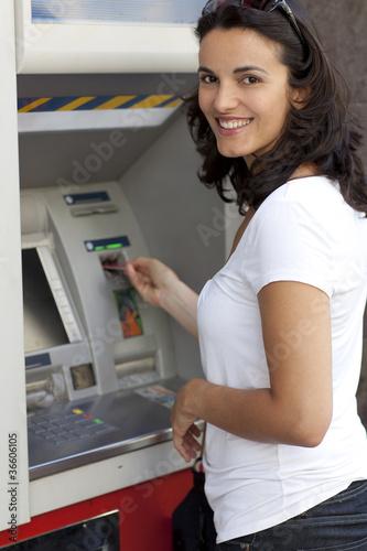 Frau führt Karte am Geldautomaten ein