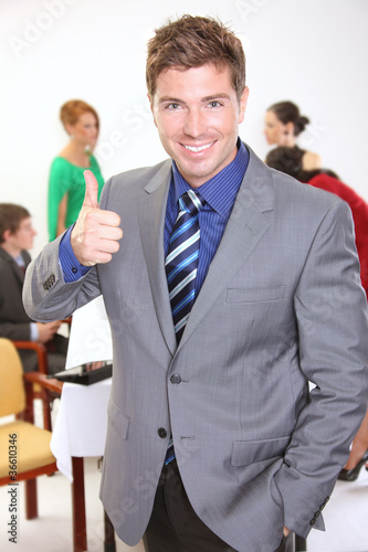 Young businessman gesturing thumbs up sign