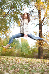girl jumping in autumn park