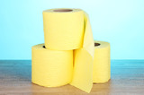 three rolls of toilet paper on wooden table on blue background