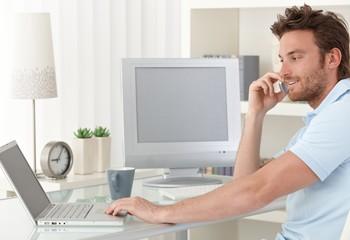Man talking on phone using computer