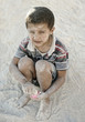 Portrait of poverty, little poor dirty boy playing in sand