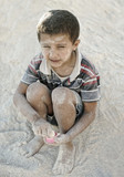 Portrait of poverty, little poor dirty boy playing in sand poster