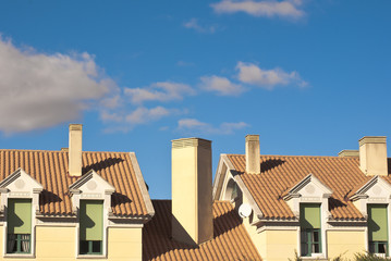 Gable Dormers and Roof of Residential House under a blue sky