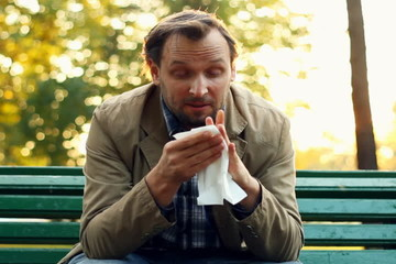 Sick man blowing his nose into tissue, outdoors
