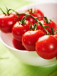 Fresh cherry tomatoes on the vine in a white bowl