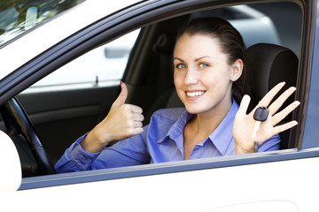 female driver in a white car showing the car key
