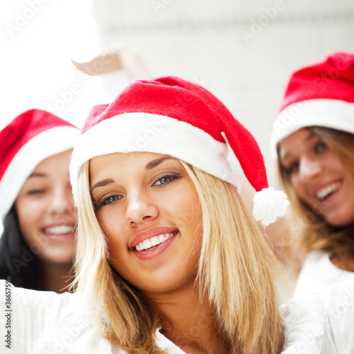 Group of three happy pretty girls are celebrating christmas