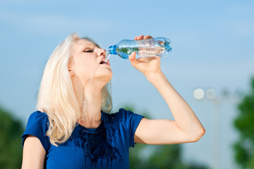Woman drinking water at outdoors sport
