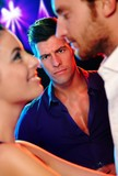 Angry man looking at loving couple in nightclub