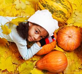 African american girl lying on pumpkin
