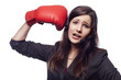 Pretty businesswoman hitting herself with boxing gloves