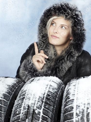 Beautiful woman with winter coat with snowy winter tyres