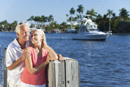 Happy Senior Couple By River or Sea with Boat