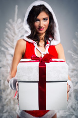 Beautiful santa woman with a gift box over winter background