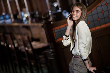 cheerful young woman talking on a cell phone in the interior of