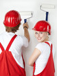 Two young worker having fun while painting a white wall
