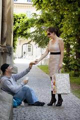 Eine reiche Frau gibt Bettler essen