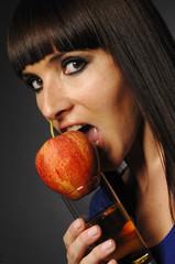 Hübsche Frau beißt Apfel und Apfelsaft in der Hand