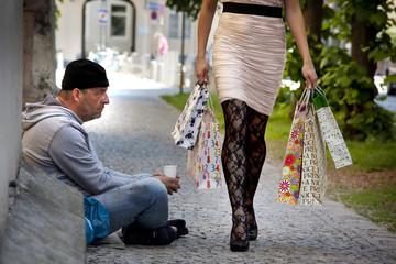 Bettler und reiche Frau beim shoppen