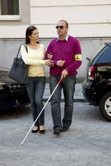 Frau hilft blindem Mann