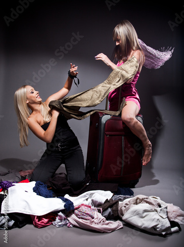 Two girls fighting holding clothes