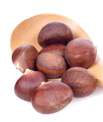 chestnuts in wooden spoon on white background