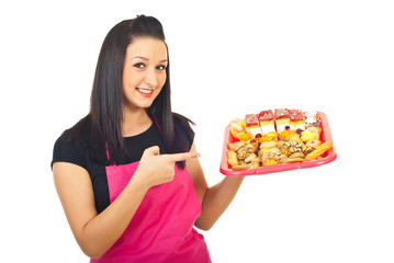 Smiling confectioner pointing to cakes