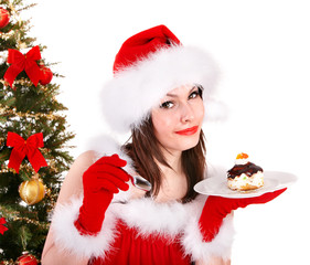 Girl in santa hat eat cake  by christmas tree.