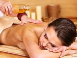 Fototapety Woman getting massage in bamboo spa.