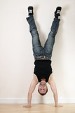 A joyful young man doing a handstand