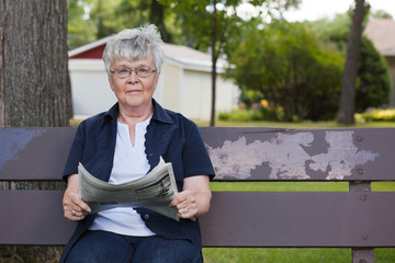Senior Woman Reading Newspaper in Park