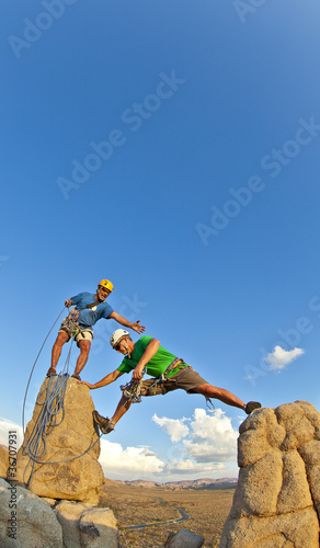 Rock climbing team reaching the summit.